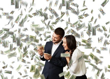 excited laughing businessman and businesswoman standing under dollars rain and counting money