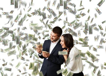 opgewonden lachen zakenman en zakenvrouw staande onder regen en het tellen van geld dollar