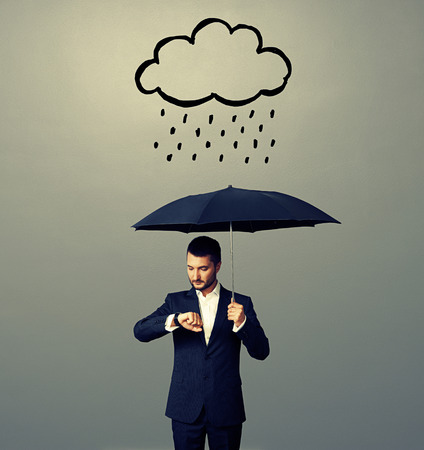 watch over: serious businessman with black umbrella standing under drawing storm cloud and looking at watch. photo over grey background