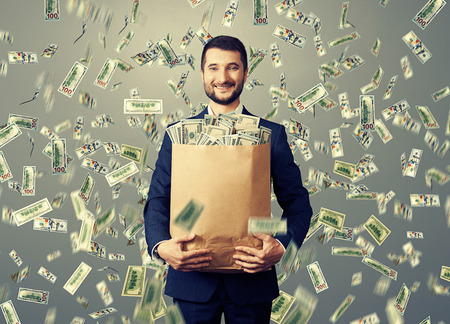 money bags: successful and smiley businessman holding paper bag with money under dollars rain