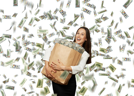 happy and smiley businesswoman holding paper bag with money under dollars rain