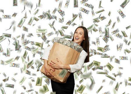 sotto la pioggia: imprenditrice azienda sacchetto di carta felice e sorridente con i soldi sotto la pioggia del dollaro