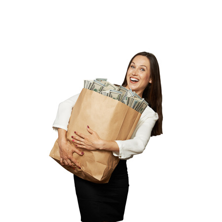 woman holding bag: excited young woman holding bag with money over white background