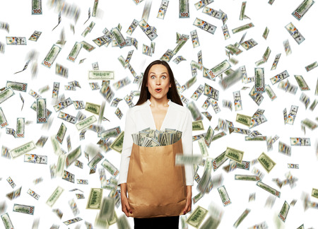 lotteries: amazed young businesswoman holding paper bag with money under dollars rain