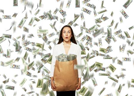 loteria: sorprendido joven empresaria celebración de bolsa de papel con el dinero bajo la lluvia de dólares