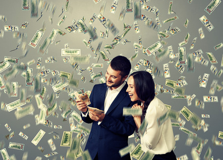 happy rich woman: happy excited couple with money standing under dollars rain