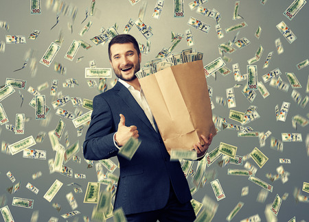 excited happy businessman standing under dollars rain and showing thumbs up Stok Fotoğraf