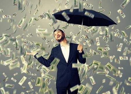 money rain: happy businessman with umbrella standing under money rain and looking up
