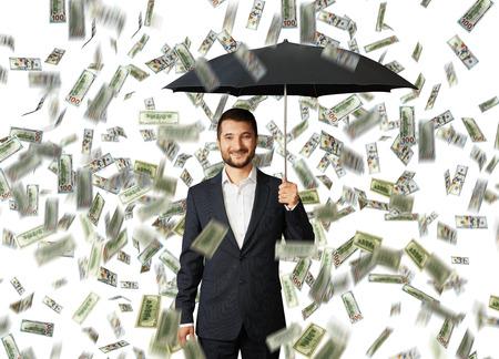 money rain: successful smiley businessman with black umbrella standing under money rain