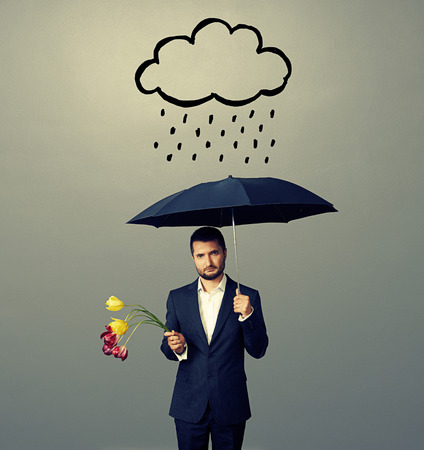 sad young man with black umbrella and drooped flowers standing under drawing storm cloud. photo over grey background Stock Photo - 29781915