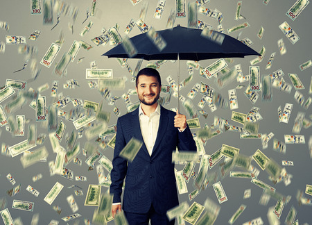 money rain: smiley glad businessman with umbrella standing under money rain Stock Photo