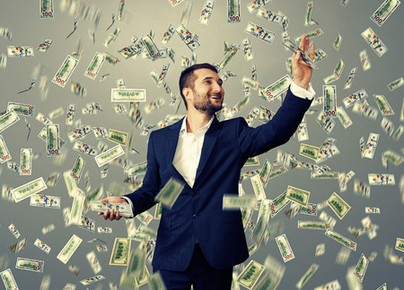 successful and smiley businessman catching money under dollar's rain Stock Photo - 29781917