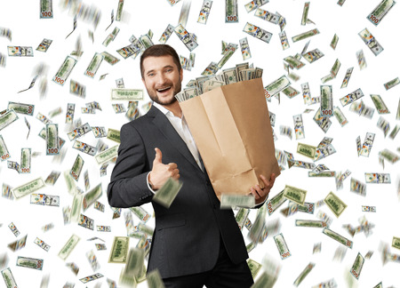 successful and smiley businessman holding paper bag under dollar's rain and showing thumbs up Stock Photo - 29781918