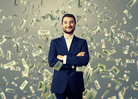 successful and smiley businessman under dollar's rain over grey background Stock Photo - 29781920