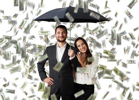 loteria: joven pareja sonriente con el paraguas negro de pie bajo la lluvia de dinero Foto de archivo