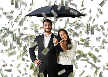 young smiley couple with black umbrella standing under money rain