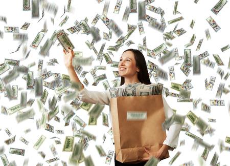 money rain: smiley successful businesswoman with paper bag catching money under dollars rain
