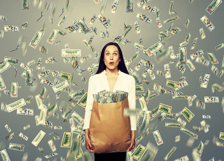 woman holding money: surprised young businesswoman holding paper bag with money under dollars rain Stock Photo