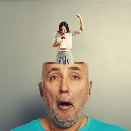 amazed senior man with open head. young emotional businesswoman standing into the head, looking at the man and screaming with megaphone. photo over grey background
