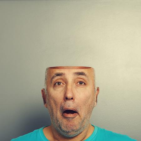 half open: concept photo of amazed senior man with open head over grey background Stock Photo