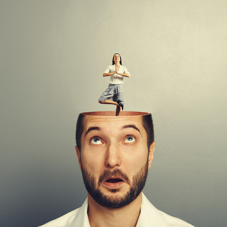 open minded: amazed young man with open head. calm yoga businesswoman standing into the head. photo over grey background Stock Photo
