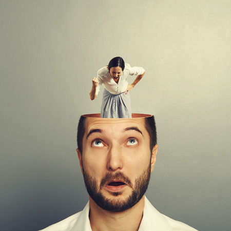 open brain: amazed businessman with open head. young angry businesswoman standing into the head, looking at the man and screaming. photo over grey background