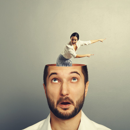 henpecked: amazed businessman with open head. young screaming businesswoman standing into the head, looking at the man and showing the direction. photo over grey background Stock Photo