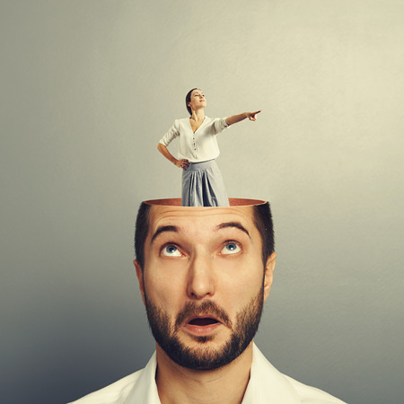 open minded: amazed young businessman with open head. young emotional businesswoman standing into the head and showing the direction. photo over grey background