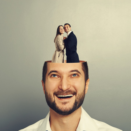 two minds: happy young businessman with open head. couple in love standing in the mans head. photo over grey background
