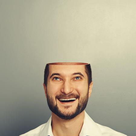 gelukkige jonge zakenman met open hoofd opzoeken en lachend over de grijze achtergrond Stockfoto