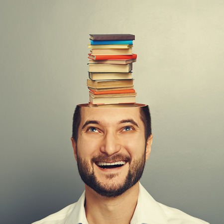 smiley young man looking up at books in the head over grey background photo