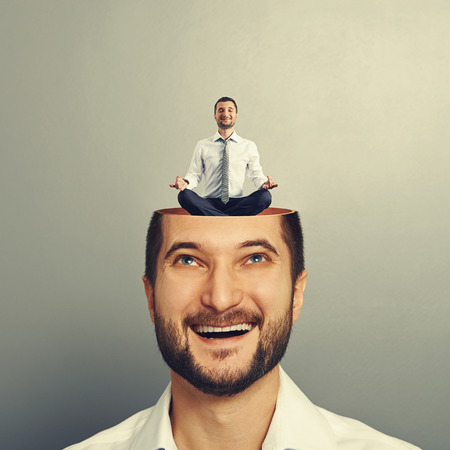 happy young businessman looking up at calm yoga man in his head. photo over grey background