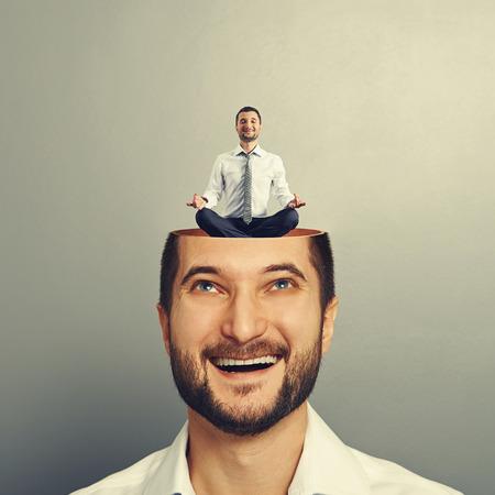 glücklichen jungen Geschäftsmann, der oben ruhig Yoga Mann in den Kopf. Foto auf grauem Hintergrund Standard-Bild