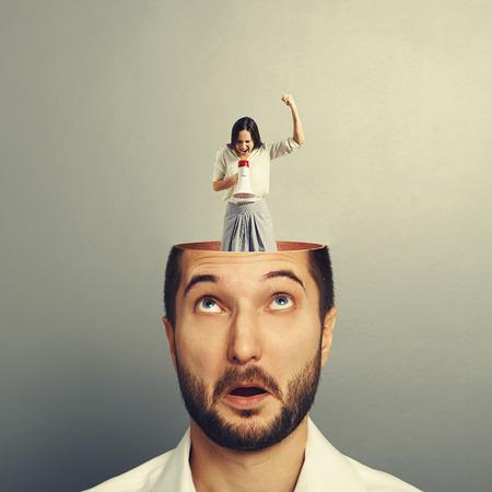 empresario sorprendido con la cabeza abierta. joven empresaria emocional de pie en la cabeza, mirando al hombre y gritando con el megáfono. foto sobre fondo gris