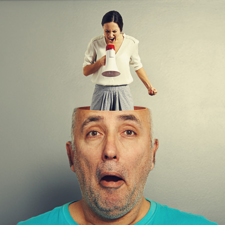 angry screaming woman in the head of amazed senior man over grey background photo