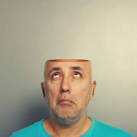 open minded: surprised senior man looking up at open head over grey background
