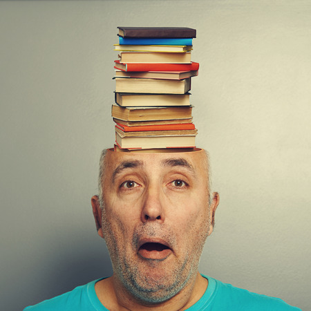 surprised senior man with books in the head over grey background photo