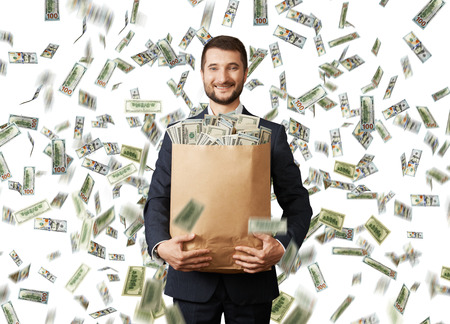 smiley young businessman holding paper bag with money under dollar's rain