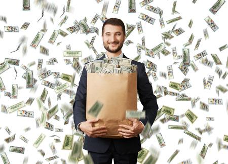 Smiley giovane imprenditore in possesso di un sacchetto di carta con i soldi sotto la pioggia del dollaro Archivio Fotografico - 30697053
