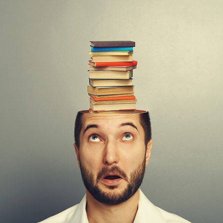 surprised young man looking up at books in the head over grey background photo