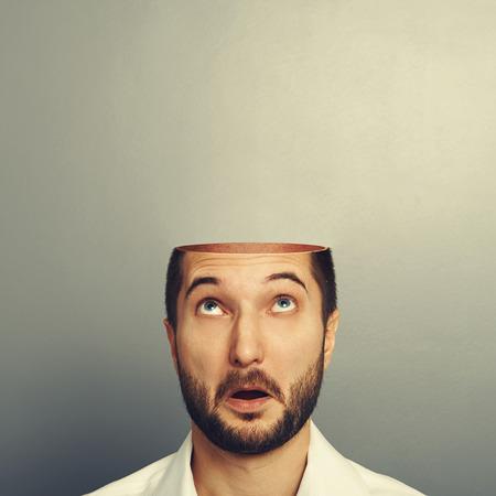 놀란 남자는 자신의 오픈 빈 머리에서 찾고. 회색 배경 위에 사진 스톡 콘텐츠