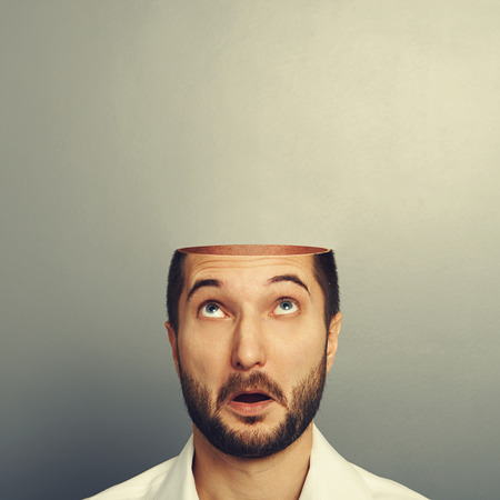 surprised man looking up at his open empty head. photo over grey background Stock Photo