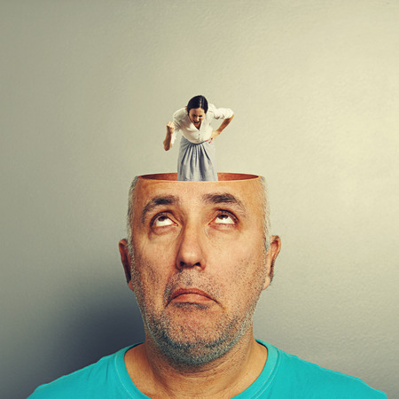 open brain: amazed senior man with open head. young angry businesswoman standing into the head, showing her fist and screaming. photo over grey background