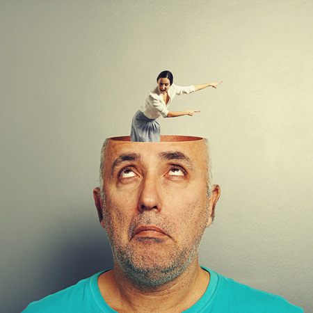 open minded: amazed senior man with open head. young screaming woman standing into the head, looking at the man and showing the direction. photo over grey background Stock Photo