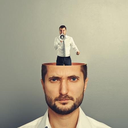 Piccolo urla e uomo arrabbiato con megafono nella testa di giovane uomo serio su sfondo grigio Archivio Fotografico - 30769261