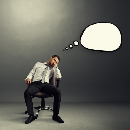 fatigued: bored businessman sitting on the chair with empty speech bubble over grey background