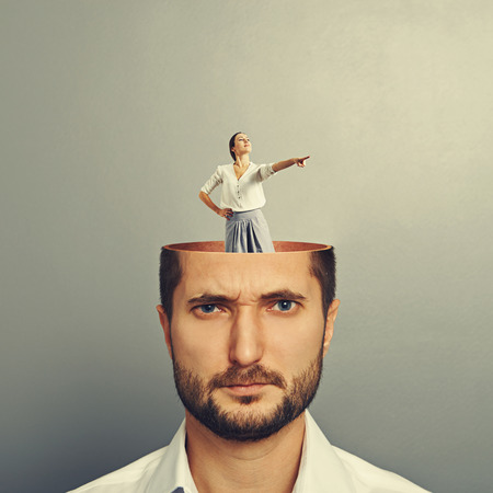displeased businessman: displeased businessman with open head. young smiley businesswoman standing into his head and showing the direction. photo over grey background