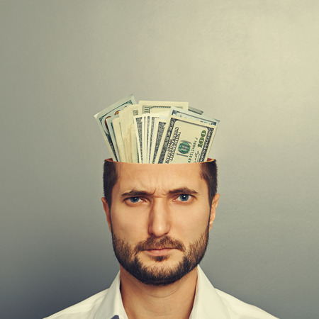 half open: young businessman with money in the head over grey background Stock Photo