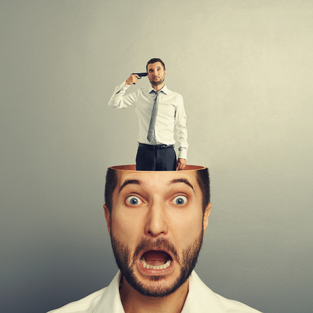 small sad man with gun standing in the head of shocked man. photo over grey background photo