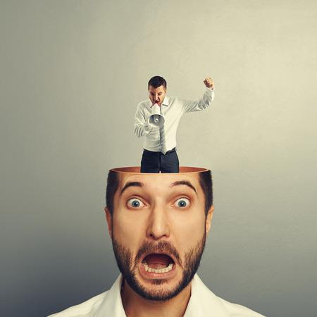 Hombre joven asustado con el hombre de grit en su cabeza sobre fondo gris Foto de archivo